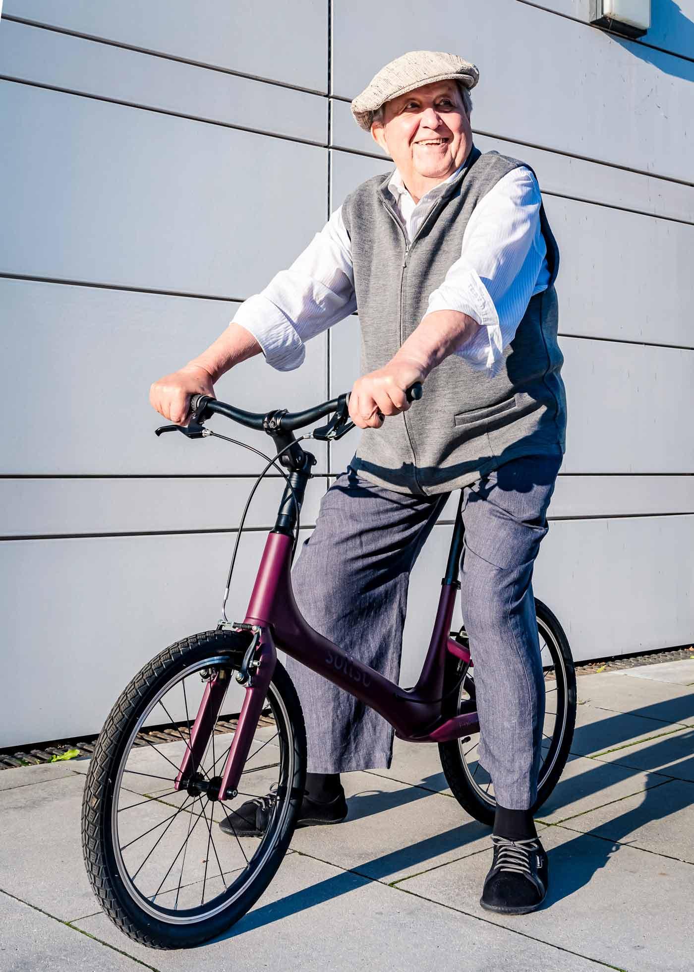Mann sitzt auf Laufrad und strahlt vor Glück
